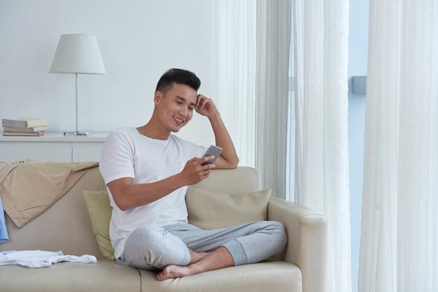 Жизнерадостный парень наслаждается свободным временем, проверяя социальные сети, удобно устроившись на диване
