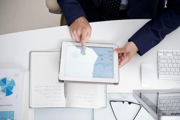 ノートブック、ドキュメント、コンピューター、匿名の男が使用するデジタルタブレットとオフィスのデスクトップのトップビュー