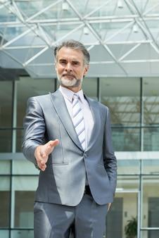 Взгляд низкого угла руки красивого бизнесмена удлиняя для приветствуя рукопожатия