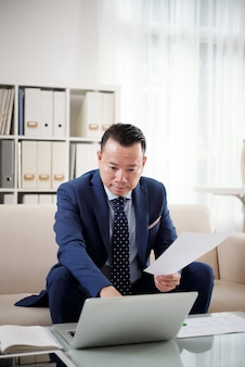 財務マネージャーは、印刷ドキュメントを参照して彼のラップトップでレポートを準備します