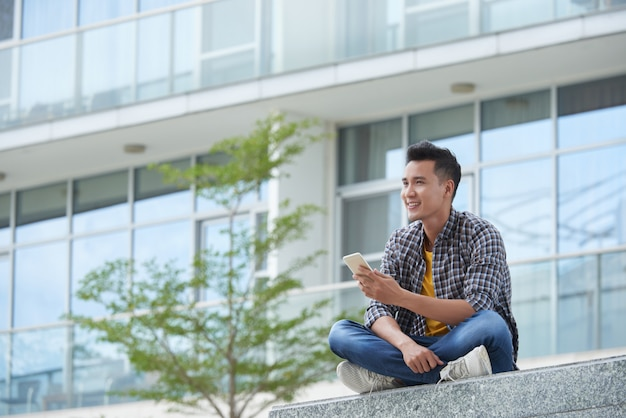 Азиатский студент, сидя на лестнице кампуса на открытом воздухе с смартфон, глядя на расстоянии