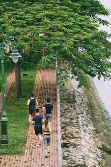 Сверху вид сзади четырех человек, бегающих трусцой в парке на берегу реки