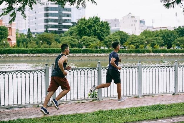 Полнометражный вид сбоку двух парней, бегающих трусцой по реке на мосту