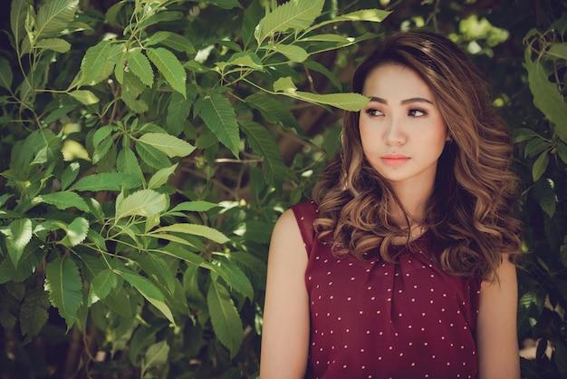 Красивая азиатская модель позирует среди листьев деревьев в парке