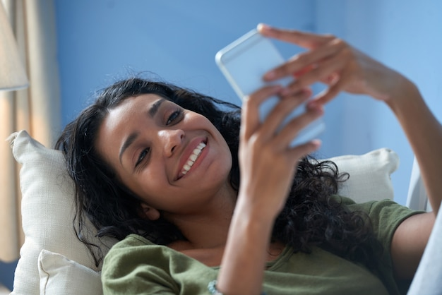 彼女のボーイフレンドへのメッセージをテキストメッセージ微笑んでいる女の子のクローズアップ