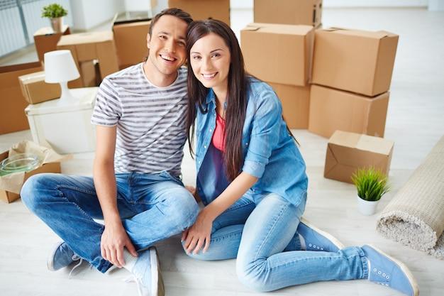 若いカップルのボックスを移動して床に座っ