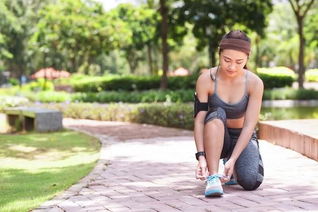 公園で靴ひもを結ぶ若いスポーツ選手