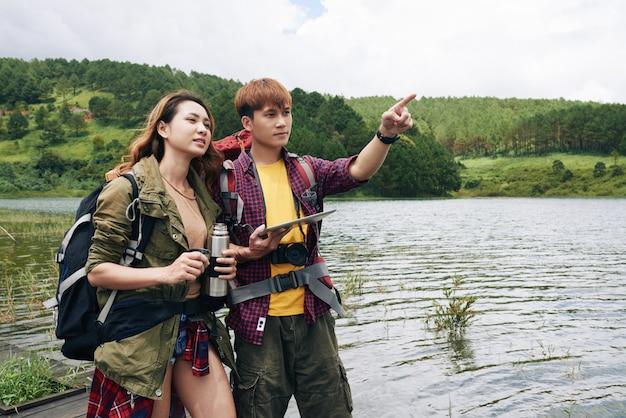 山の方向のデジタルタブレットの地図を使用してアジアの若いカップル