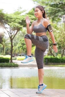 Тренировка жизнерадостной спортсменки в парке