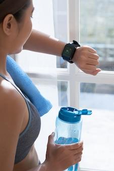 スマートな時計を見ている女性をトリミングします。