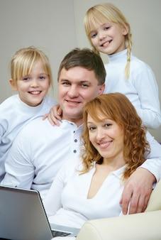 自宅でソファに座って笑顔の家族