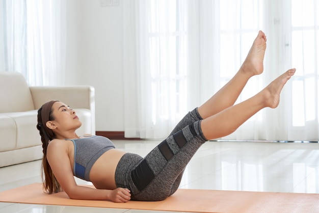 マットの上の陽気な女性トレーニング腹筋
