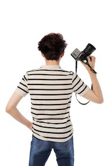 カメラに背を向けて立っているカメラを持つ男のミディアムショット