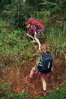 丘を登ろうとしている女性ハイカーに救いの手を差し伸べる男性ハイカーのフルショット