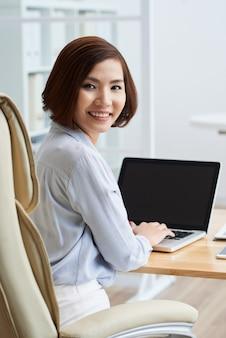 オフィスの机でキーボードで入力して彼女の手でカメラを見て回るビジネス女性の肖像画