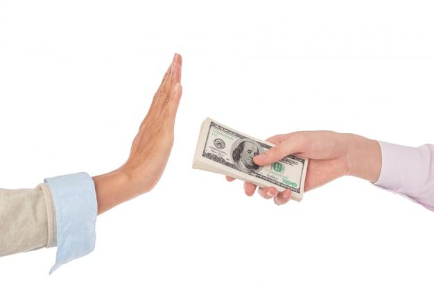 ドル札の山をお金を拒否するかのように身振りで示す男性の手に広げる女性の手のクローズアップ