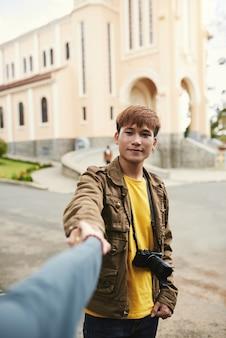 Средний снимок портрет азиатского парня с фотоаппаратом, держа руку неузнаваемой женщины