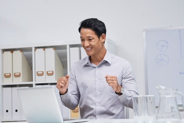 Талия вверх портрет азиатского бизнесмена, сидя на рабочий стол, глядя на экран ноутбука
