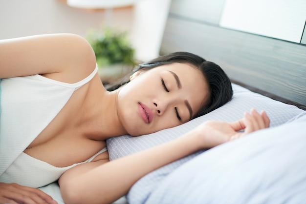 Молодая спящая женщина на кровати