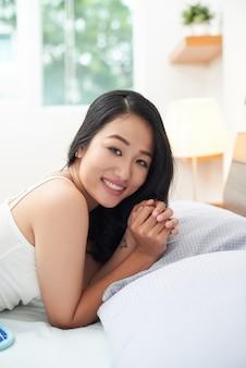 ベッドで横になっているかなり民族の女性