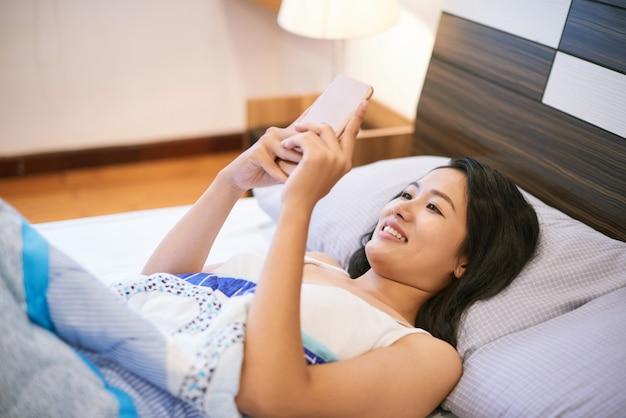 女性がベッドに横たわっている間電話を使用して
