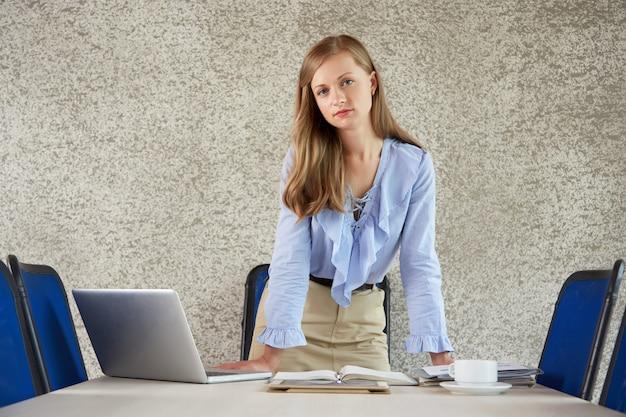 Средний снимок деловой женщины, стоящей на офисном столе и смотрящей на камеру
