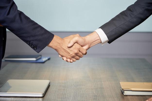 会議で握手する人々を切り取る