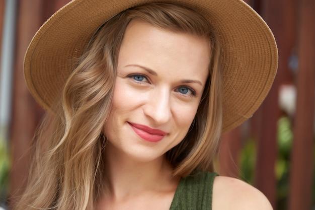 麦わら帽子の若い若い女性のクローズアップの肖像画