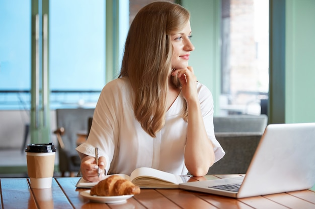 Молодая женщина, сидя за столом, держа перо и глядя в окно