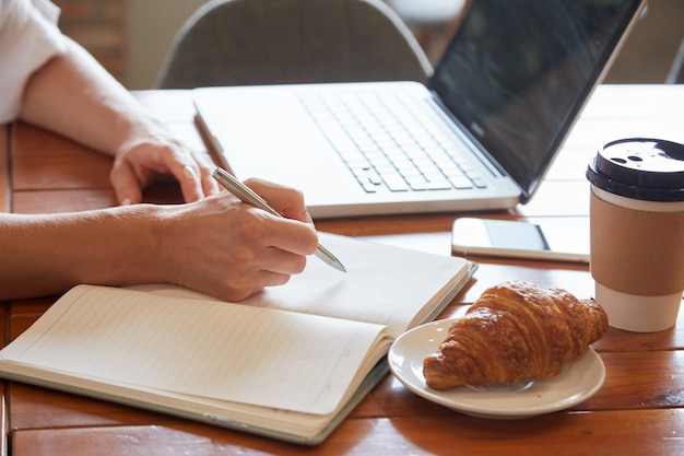 Крупным планом стол для завтрака с женскими руками, положив информацию для ежедневника