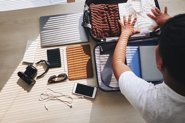 旅行用スーツケースを梱包している認識できない男、および近くに横たわる電子機器