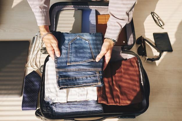 認識できない男の出張のためのスーツケースを梱包