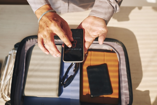 Неузнаваемый мужчина упаковывает чемодан и использует смартфон