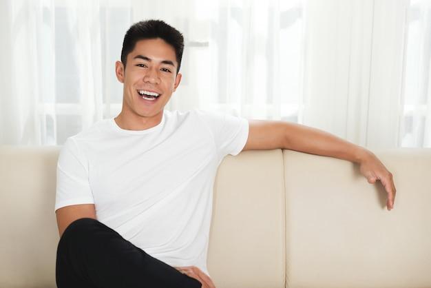Веселый молодой азиатский человек, сидя на диване у себя дома