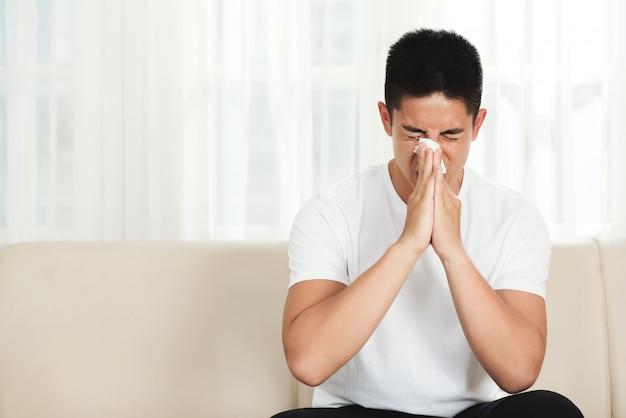 Молодой азиатский человек сидя на кресле дома и дуя нос с тканью
