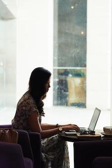 Азиатская женщина сидит за столом в кафе с ярким окном и работает на ноутбуке