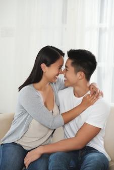 愛する若いアジアカップルハグとお互いを見て