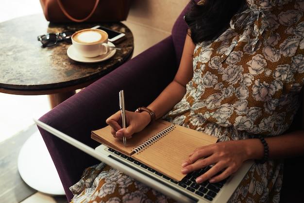 До неузнаваемости женщина сидит в кафе с ноутбуком и пишет в тетради