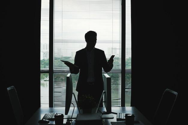 オフィスの窓に立っているとタブレットとスマートフォンを保持している実業家の暗いシルエット