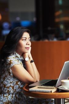 Мечтательная красивая молодая азиатская женщина сидя в кафе с компьтер-книжкой