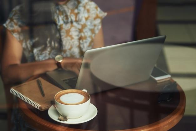 До неузнаваемости молодая женщина сидит за столом в кафе и работает на ноутбуке
