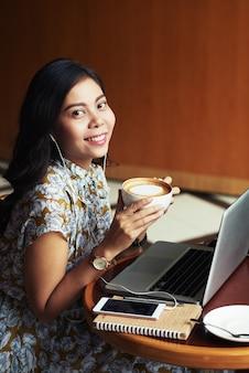 カフェでラップトップで座っているとカプチーノを楽しんでいる若いアジア女性