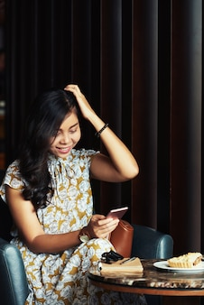 Молодая азиатская женщина сидит в кафе, смотрит на смартфон и смеется