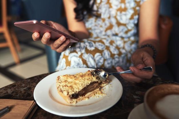 До неузнаваемости молодая женщина сидит в кафе, с помощью смартфона и ест крошить пирог