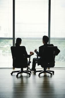 窓の前のオフィスの椅子にマグカップと座っている男女の暗いシルエット