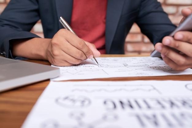 スマートフォンでテーブルに座って、紙の上のビジネス図を描画認識できない男
