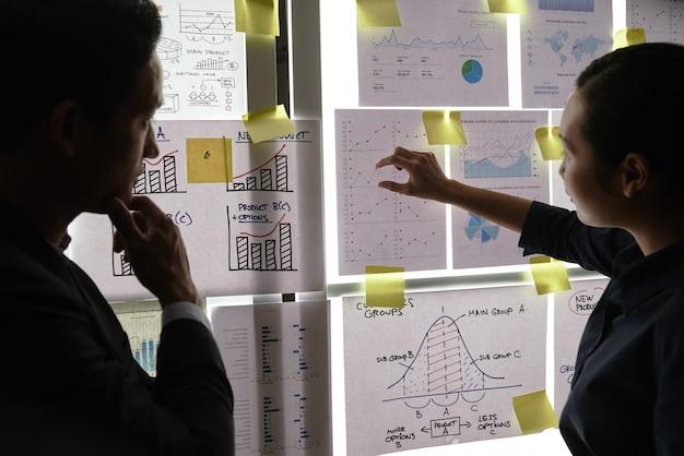 Мужские и женские коллеги, стоя у окна и глядя на бизнес-графики на нем