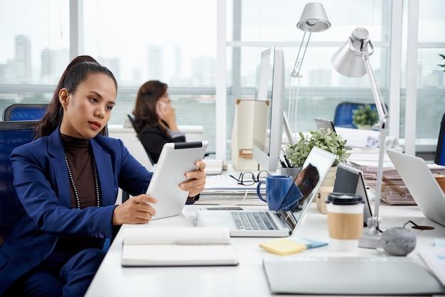 Шикарно одетая азиатская женщина сидя на столе в офисе с таблеткой