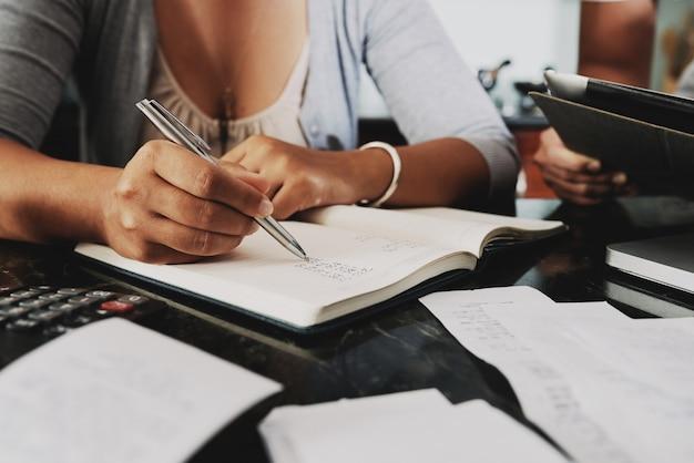 認識できないカップルが領収書で家に座って、費用を数える