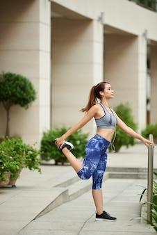 通りに立って、トレーニングの前にストレッチスポーツウェアの若いアジア女性